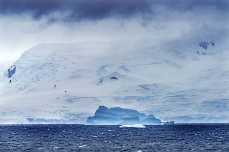 Blue Iceberg Glaciers Charlotte Bay Antarctic Peninsula Antarctica.  Glacier ice blue because air squeezed out of snow.