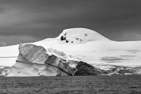 Blue Iceberg Glaciers Mountains Charlotte Bay Antarctic Peninsula Antarctica.  Glacier ice blue because air squeezed out of snow. Stock fotó