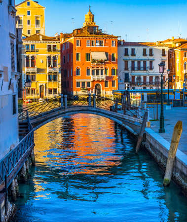 Colorful small canal and bridge creates beautiful reflections in Venice Italy