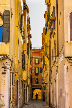 Old Narrow Street Calle Pasqualig High Walls Neighborhood Houses in Venice Italy.