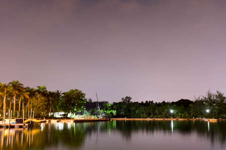 Horizontal view of lake and nature during dusk with night stars and smooth reflection on waters somewhere in Asia