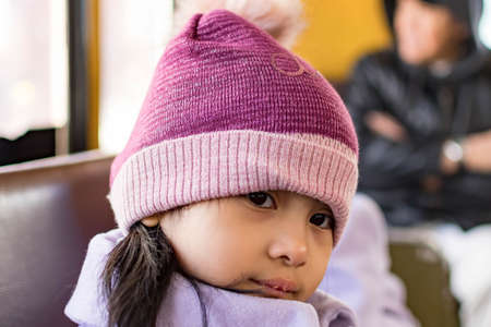 Pretty female child wearing purple coat and cute bonnet while sitting inside a bus and sleepy, Her lips are dry because of the cold weather Banque d'images - 144172675