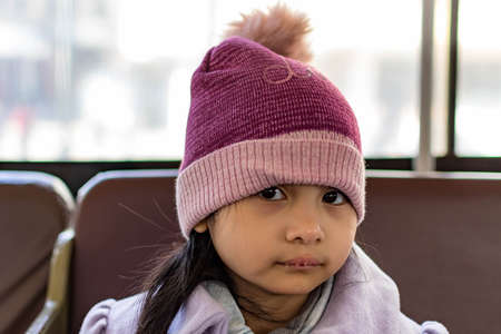 Pretty female child wearing purple coat and cute bonnet while sitting inside a bus and sleepy, Her lips are dry because of the cold weather Banque d'images - 144173003