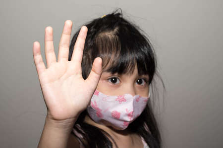 Kids hand to say no against corona virus infection. Blurry image of a female kid showing her hand to symbolize against the spread of corona virus
