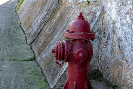 Old red water hydrants on a street with old brick wall background. Vintage water hydrant found on an old street
