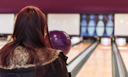 A bowling ball while being aimed to the target by a female adult in a bowling tournament. Purple  bowling ball and blurry bowling alley background