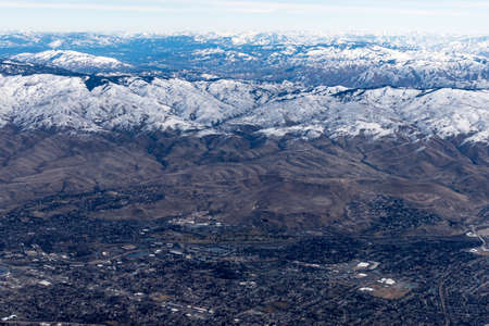 Aerial View of Idaho mountains from the sky while inside an airplane. View of brown mountains and trees covered with snow