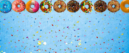 colorful donut with sprinkle on blue background. Background image with copy space