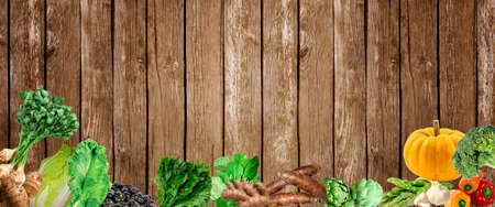 Table scene with a variety of fresh vegetables. Overhead view on a rustic wood background.