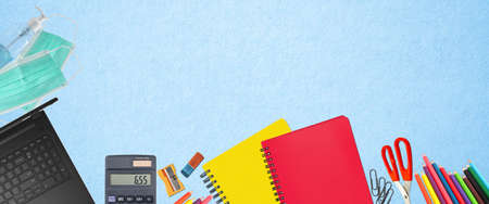 School supplies and covid 19 prevention items. Bottom border on a light blue soft background. Back to school during pandemic concept with copy space.
