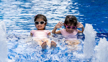 Portrait of pretty asian twins smilling and posing on swimming pool background wearing pink swim suit and sun glasses