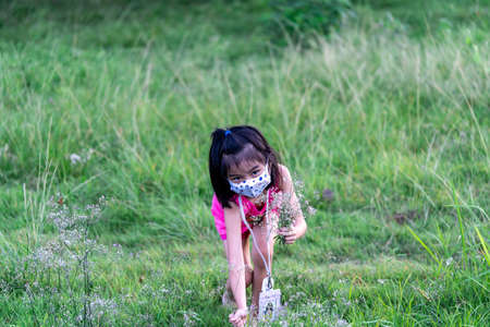 Pretty child playing picking up flowers in a farm while wearing mask