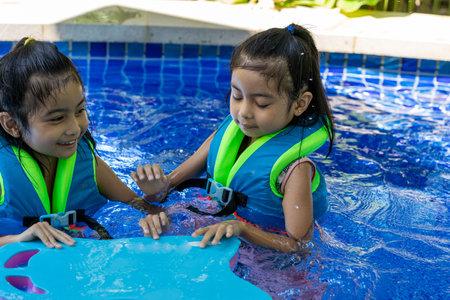Pretty asian children while swimming wearing vest on a swimming pool. Pretty asian twins while swimming Stock Photo