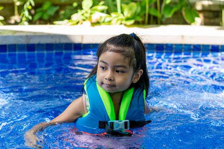 Asian child smilling wearing vest on a swimming pool enjoying swim Stock Photo
