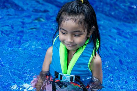Pretty asian child smilling while wearing a vest in a swimming pool during swimming lesson Stock Photo