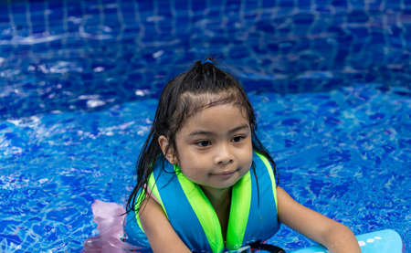 Asian child looking while wearing life vest in a swimming pool Stock Photo