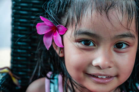 Little girl with large pink flower behind ear. Pretty asian child portrait with flower behind ear