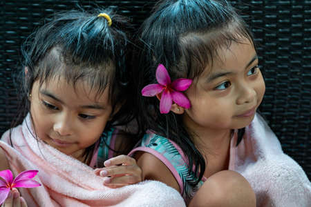 Little girl twins with large pink flower behind ear