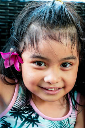 Little girl with large pink flower behind ear. Pretty asian child portrait with flower behind ear smiling