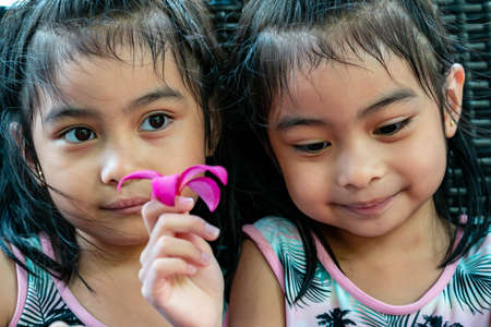 Pretty child twins holding a pink flower. Pretty asian twins portrait with flower and smiling Stock Photo