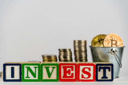 Money coins stack stair as step growing growth and wooden cube block with word INVEST. Investment and save money concept. Invest on bitcoin. Invest on crypto Stock Photo
