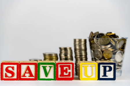 Money coins stack stair as step growing growth and wooden cube block with word SAVEUP. Investment and save money concept. save up money. save up on savings