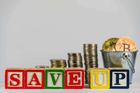 Money coins stack stair as step growing growth and wooden cube block with word SAVEUP. Investment and save money concept. save up on bitcoin. save up on crypto