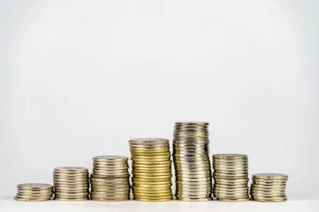 Seven stacks of golden coins with different heights arranged in growing direction, isolated on white background Stock Photo