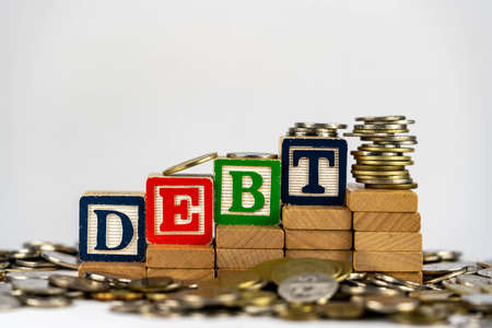 Debt concept with wooden blocks and coins. Debt letters on wooden blocks sorrounded with money