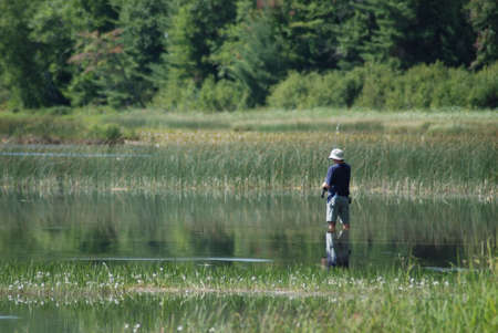shallow water: Fishing man standing in shallow water