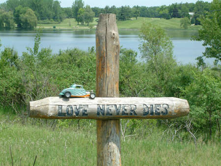 Wooden memorial cross next to lake