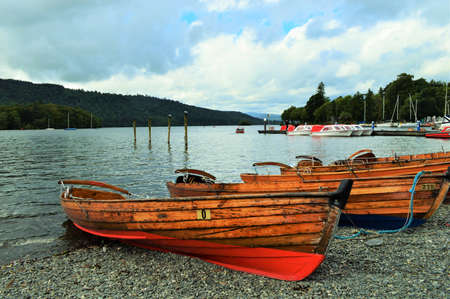 rowboats: Wooden Rowboats on shore of lake in England Editorial