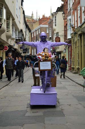 performer: Purple Street Performer on Bike Editorial