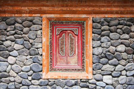 traditinal: A style of window inside a wall of rock in Tanganan traditinal village in Bali, Indonesia Stock Photo