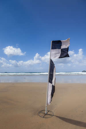 Sunny beach with flag and blue sky photo