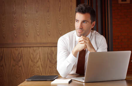 Good looking businessman put hands together and looking outside the window thinking about project. Stock Photo Foto de archivo