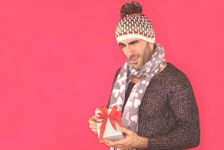 Handsome caucasian guy holding gift box standing in fron of pink background. Imagens