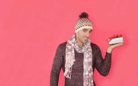 Handsome caucasian guy holding gift box standing in fron of pink background. Stock Photo