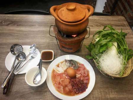 Clay pot with meat dish and vegetable. Thai food
