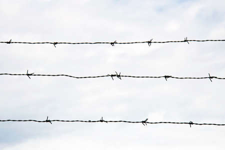 An barbed wire security fence aganst sky Фото со стока