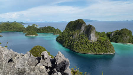 Green rock island in the middle blue lagoon and behind of artistic grey stone