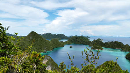 Beautiful landscape of bunch of hills surrounded clear tosca water and bright blue sky  and white clouds