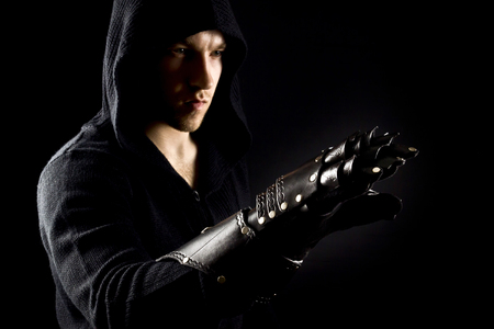Emotional, young and attractive assassin in gloves on the black background