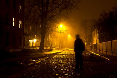 Un uomo sulla strada nebbiosa di notte Archivio Fotografico