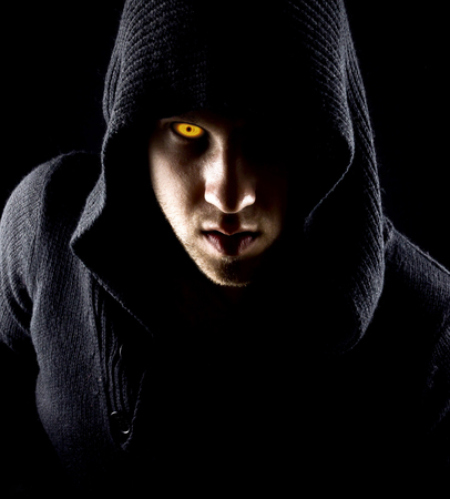 Emotional, young and attractive assassin in gloves on the black background Stock Photo