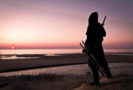 Assassin en costume noir avec épée debout sur la plage. Banque d'images