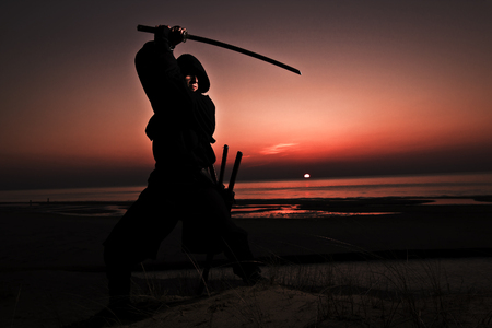 Assassin in black suit with sword working out at the beach.