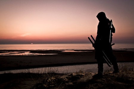Assassin in black suit with sword standing at the beach.