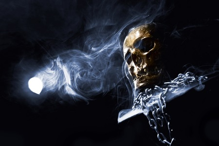 Close up of skull on black background around smoke and with chain.