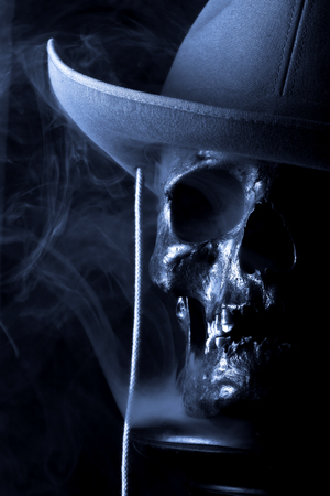 Abstract anatomy - humans skull in cowboy hat on black background with smoke around it.